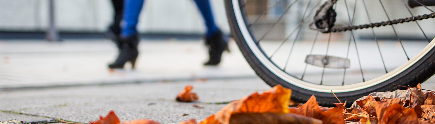 A bike wheel, a woman walking and some leaves on the ground