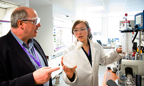 Female researcher wearing white lab coat discussing experiment with man in suit