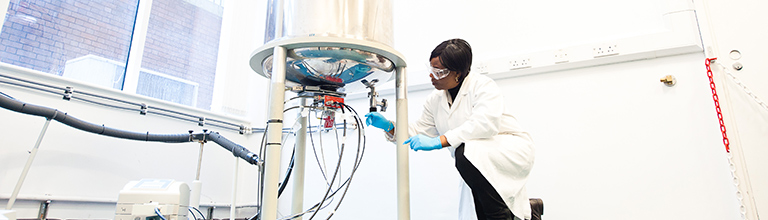 Female researcher wearing white lab coat adjusting apparatus