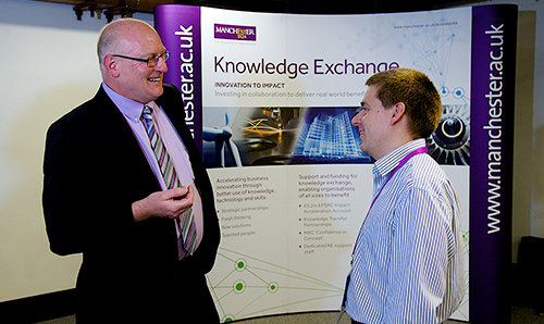 Suited men in conversation at 'Knowledge Exchange' event