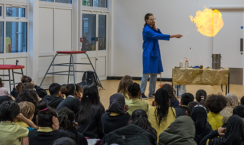A researcher creating a ball of fire for a room of primary school children