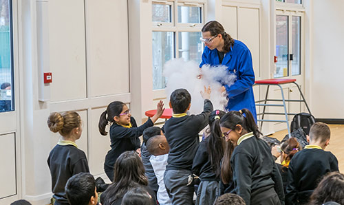 A researcher creating smoke for a group of primary school children
