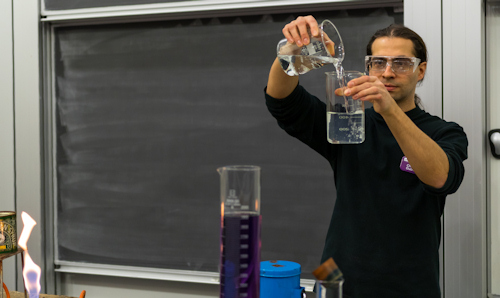 Lecturer pouring chemicals between beakers in front of a blackboard