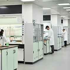 A number of researchers in lab coats working away in the lab