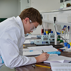A male researcher in lab coat writing down notes