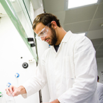 A male researcher in lab coat concentrating on his work