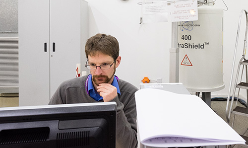 A male researcher using NMR equipment in the University