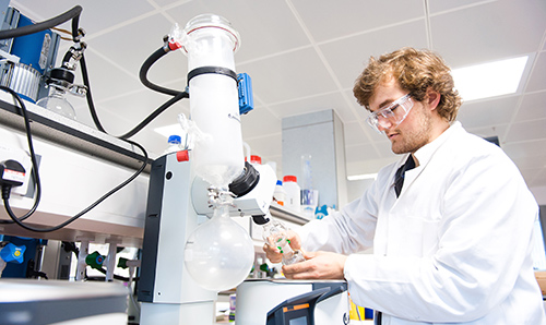 Student in white lab coat performing experiment in lab