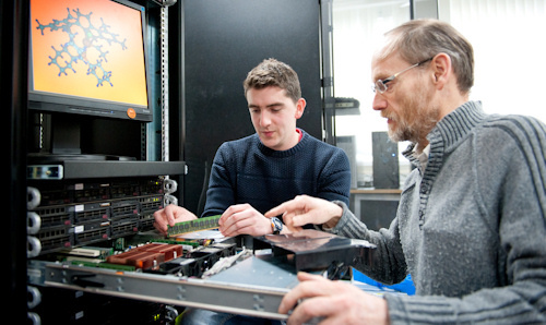 Student and lecturer installing memory chip into computer
