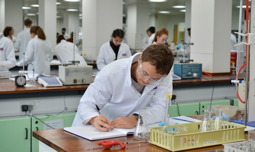 A male researcher in a lab coat with his head down writing