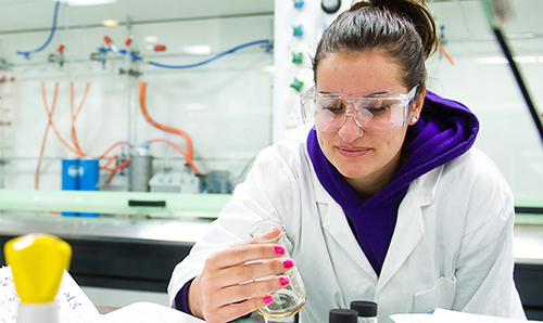 Female student examining a beaker during an experiment