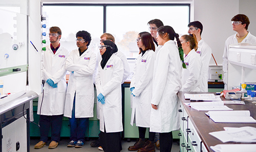 A number of students in lab coats watching a demonstration