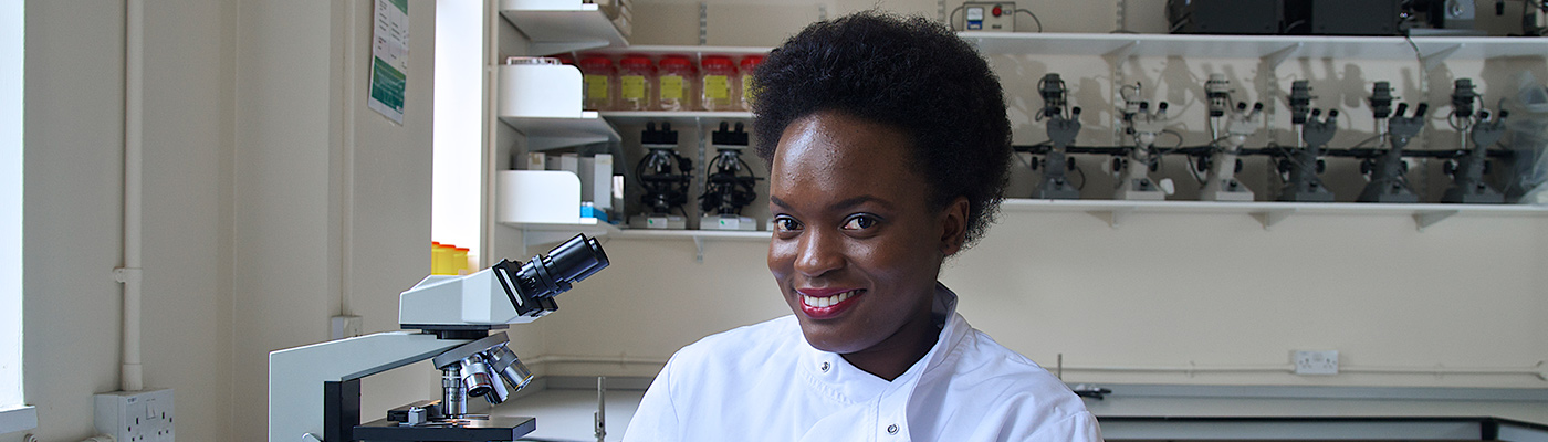 Female student wearing lab coat smiling at camera in laboratory