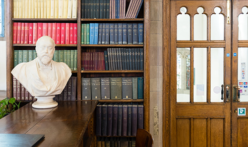 A bust of a man's head and shoulders in front of a shelf of library books