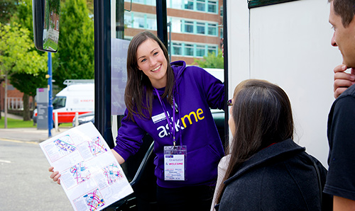 Female student wearing Askme hoodie welcoming prospective students on open day