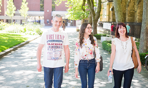 Parents and student smiling while walking through campus on open day
