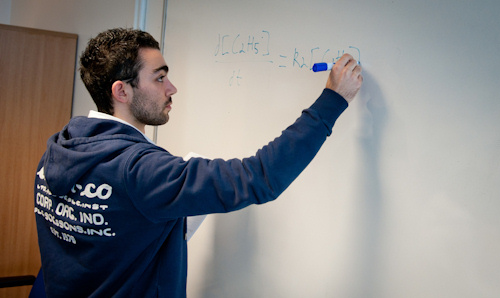A researcher writing a formula on a whiteboard