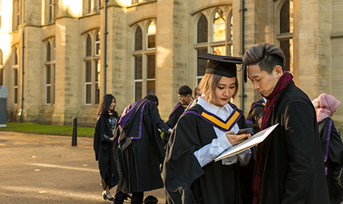 A newly graduated couple stand in graduation gowns outside Whitworth Hall