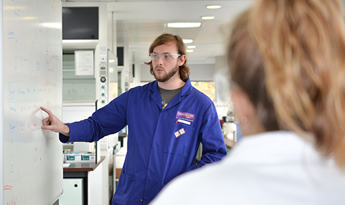 Student in blue lab coat explains content of whiteboard