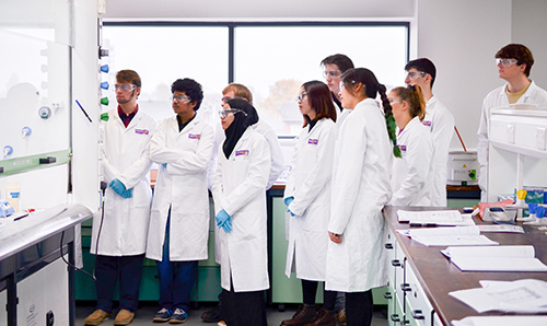A row of students wearing white lab coats and goggles observe an experiment in a lab