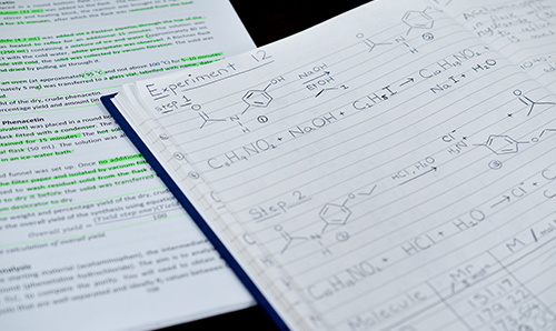 A close-up of chemistry formulas and workings on a notepad