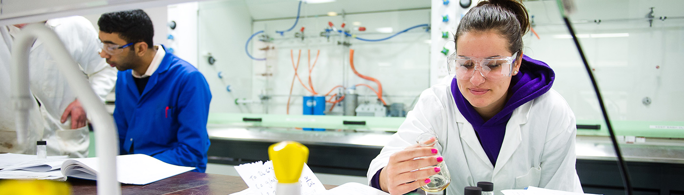 Female student in safety glasses examining a solution in a beaker