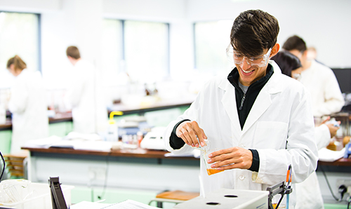 A male researcher in a lab coat smiling down at his experiment
