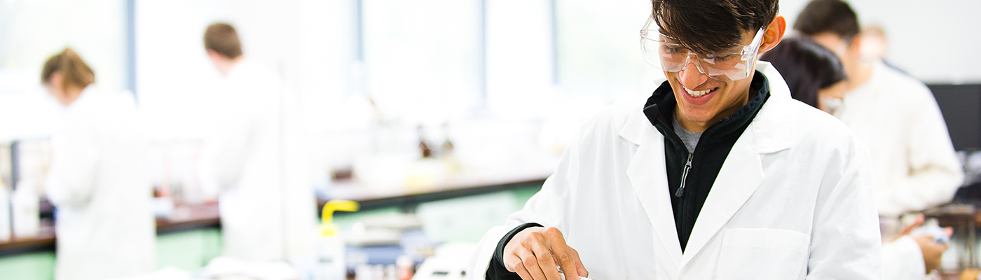 A male student in a lab coat smiling as he works on an experiment