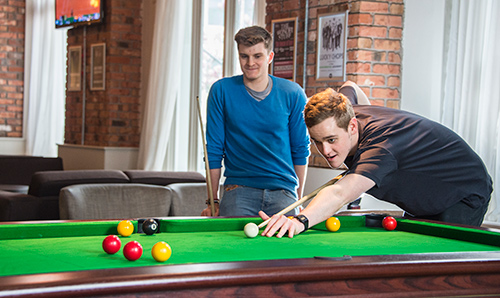 Two male student playing pool in the students' union