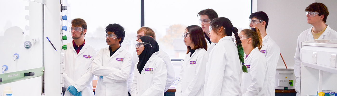 A group of students in lab coats watching a demonstration